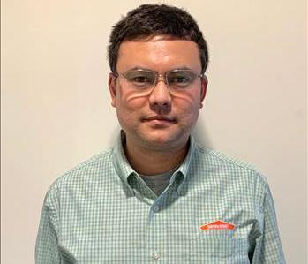 Man with dark hair and sliver-framed glasses with SERVPRO labeled shirt