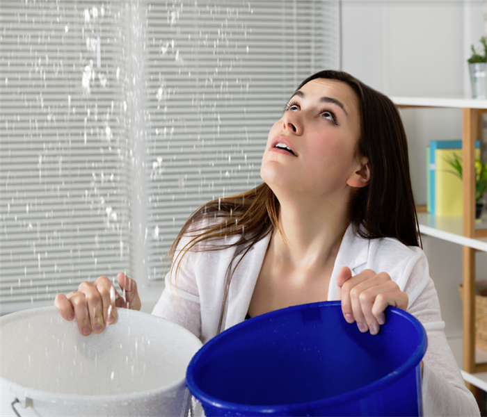 a woman holding two buckets to try and catch water leaking from the ceiling